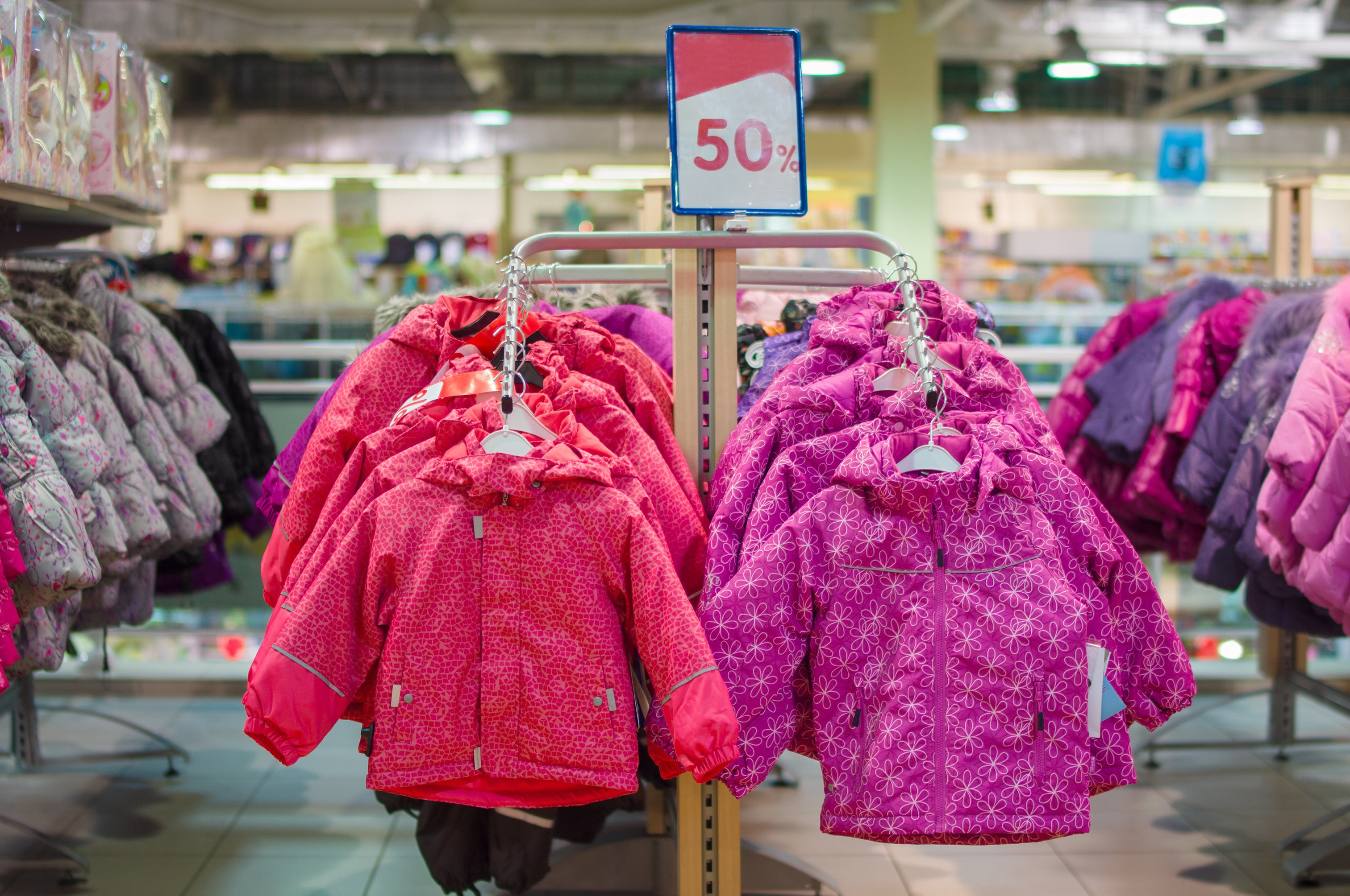 Winter jackets for kids on stands in store